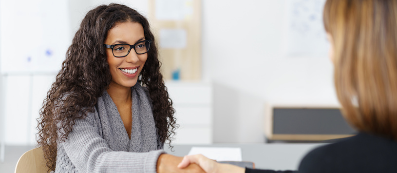 A curly haired woman smiling and shaking hands with the admissions advisor. Go to SUI – a Sonography School in Sacramento.