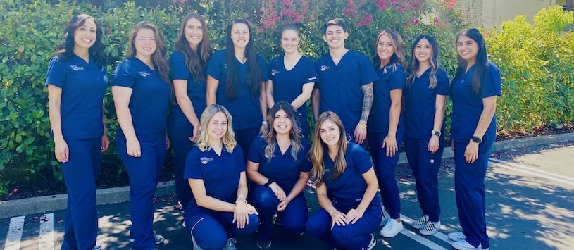 A group shot of SUI students wearing blue scrubs