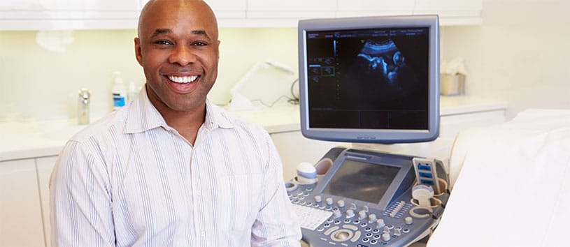 A man smiling in front of a sonography machine.
